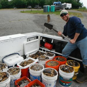 Capt Mike posing with many buckets of clams